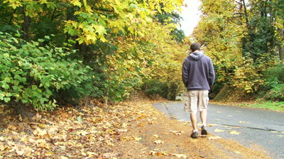 Man-walks-away-down-street-full-of-autumn-leaves