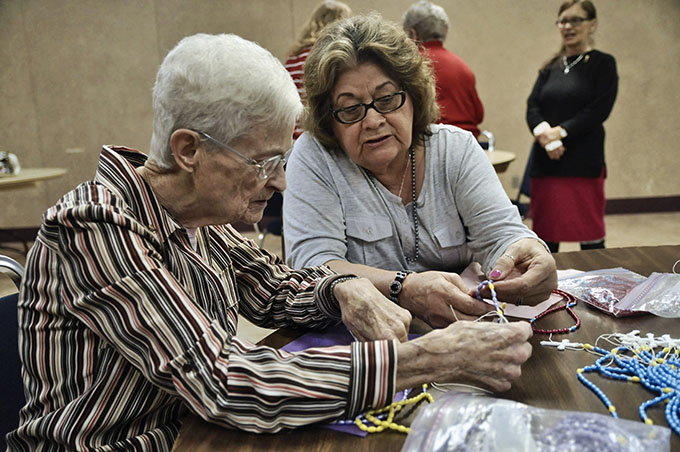 Parishioner Micaela Olivarez, right, shows Philomena Mattingly, how to put together a holiday rosary at Holy Spirit Catholic Church Dec. 2.
