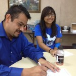 Alberto Torreblanca fills out form 100 as daughter Lissette looks on